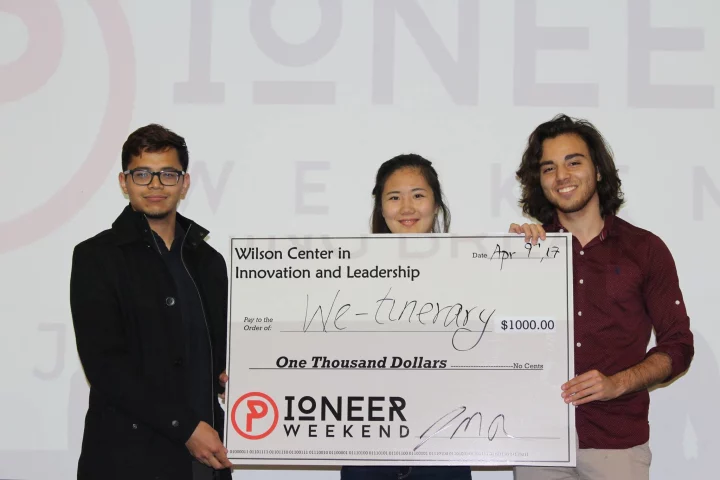 Photo of three students with large check written out the We-tinerary for $1000